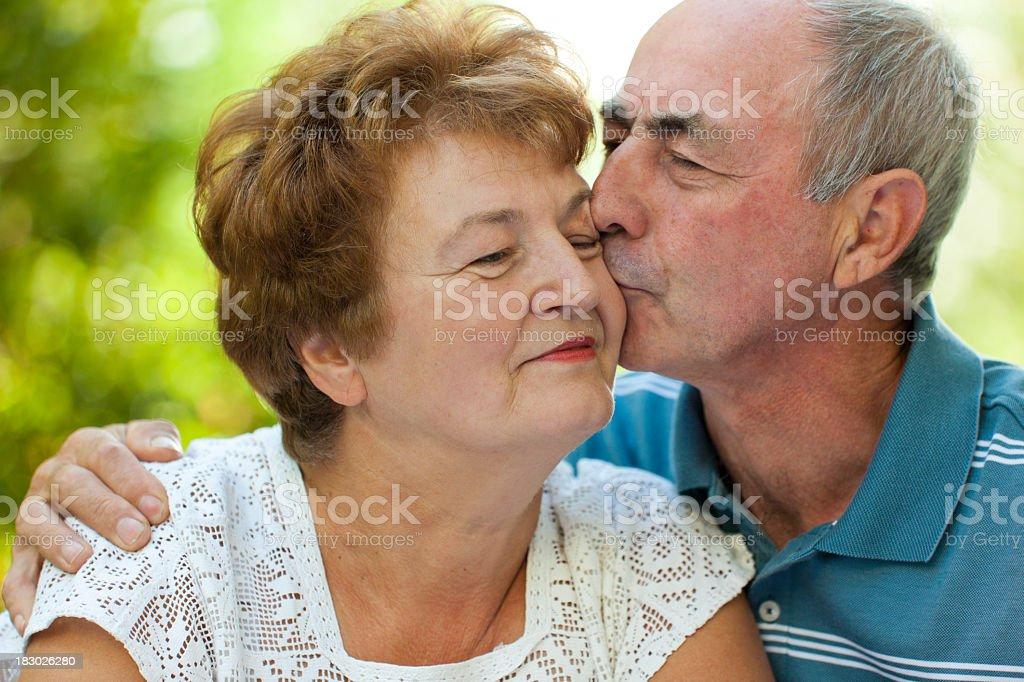 Senior husband kissing his wife stock photo