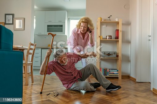istock Senior husband  sitting on floor while retired  wife  talking on smartphone 1156343650