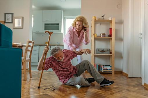 istock Senior husband  sitting on floor while retired  wife  talking on smartphone 1156343650