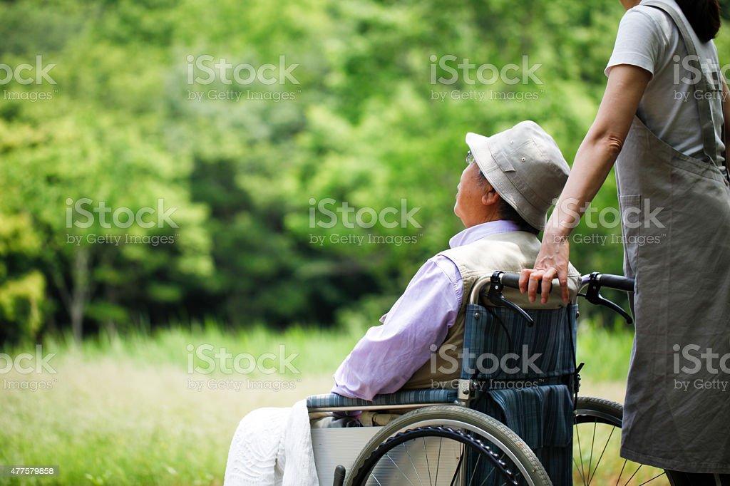 Sênior em cadeira de rodas e ajudante - foto de acervo