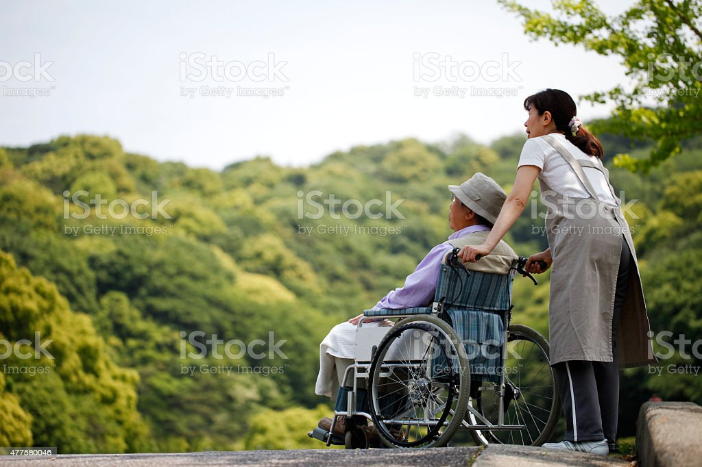 Senior in a wheelchair and helper stock photo