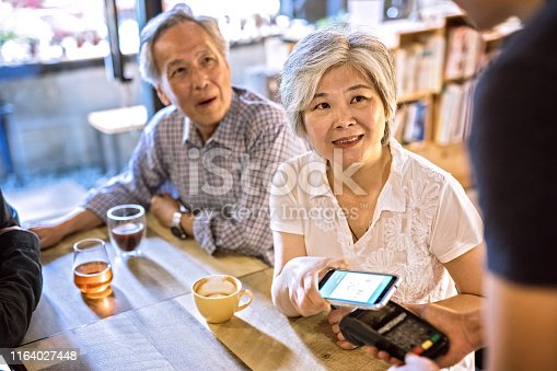 Senior Adults Having tea And Spending Free Time Together at Bar, Contactless payment