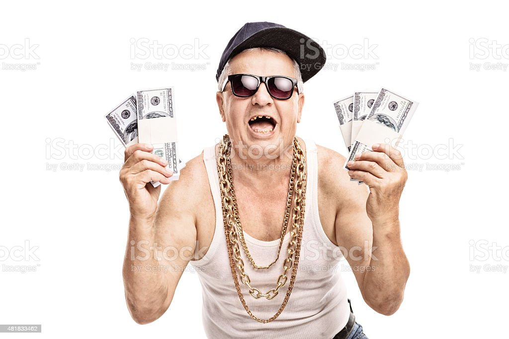 Senior in hip hop outfit holding few stacks of money stock photo
