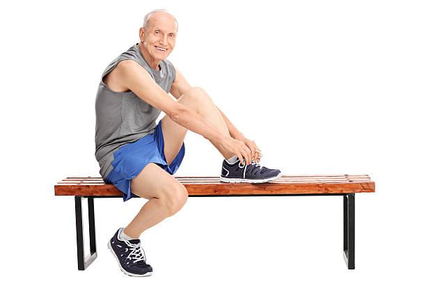 senior in sportswear seine schnürsenkel binden - sitzbank schuhe stock-fotos und bilder