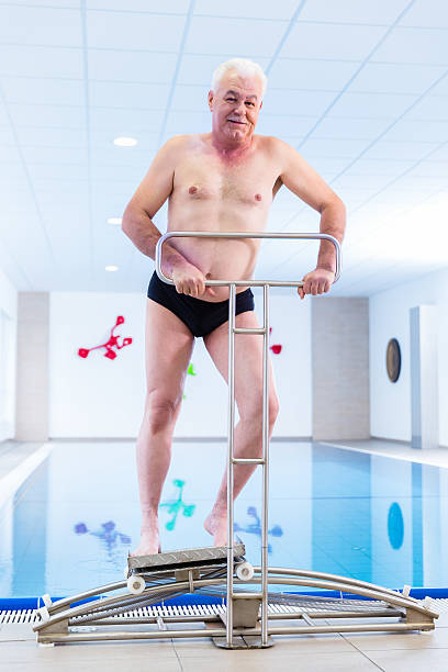 Senior in water gymnastics therapy stock photo