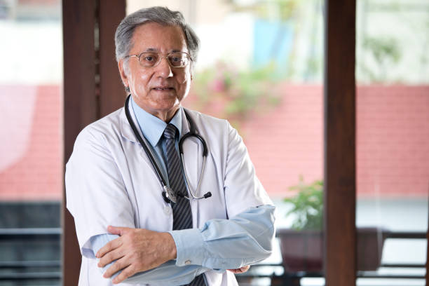Senior Indian doctor looking at camera stock photo
