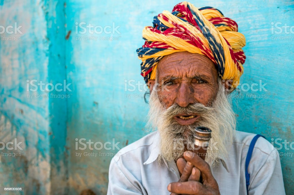 Senior indian man with vibrant colorful indian turban holding his...