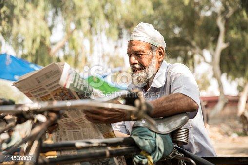 Senior Indian Man Reading Newspaper Outdoors