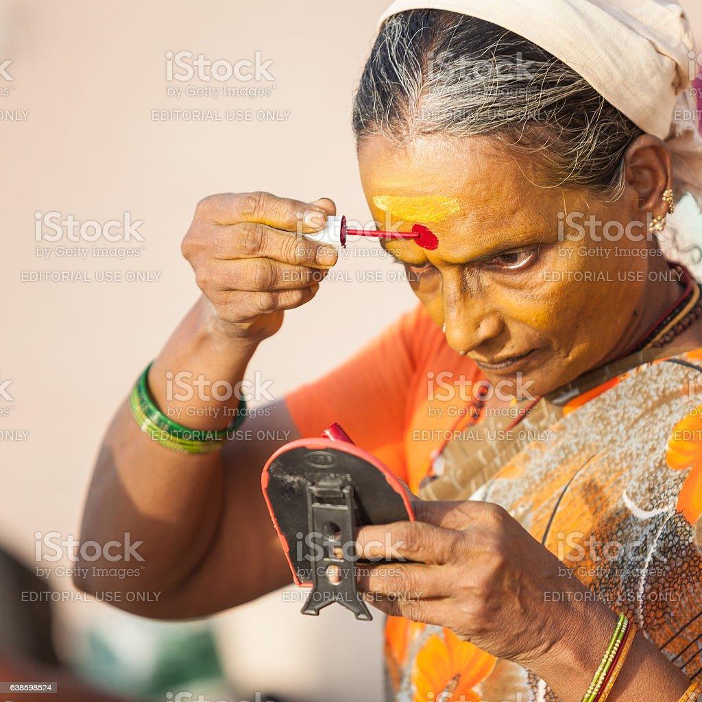 Senior Indian Woman Painting Bindi On Her Face stock photo