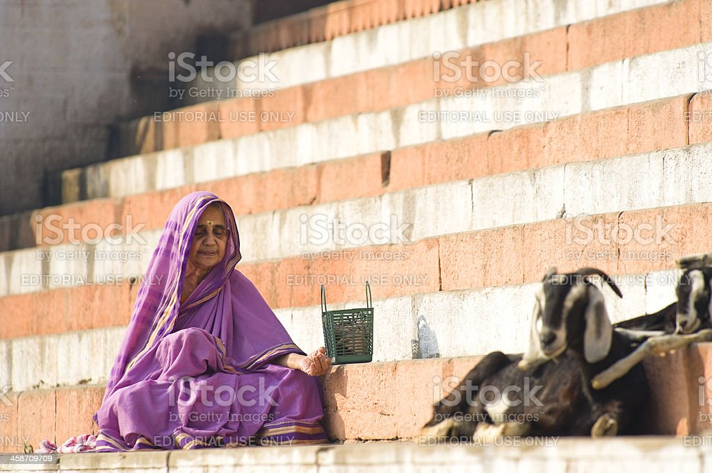 Senior Indian woman praying in front of colorful ghat, Inida royalty-free stock photo