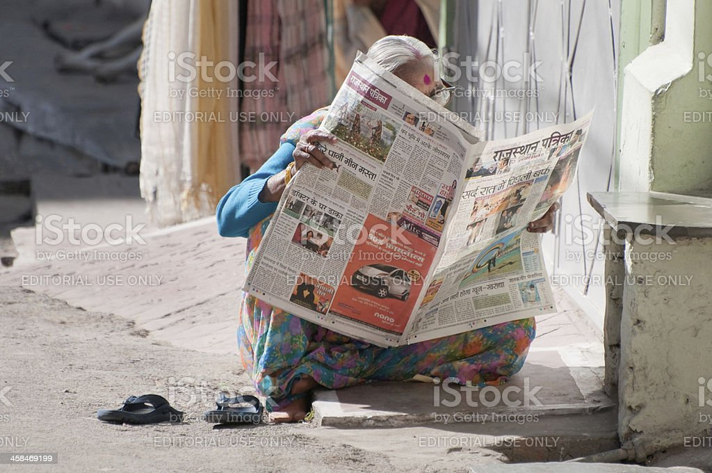 Senior Indian woman reading the newspaper stock photo
