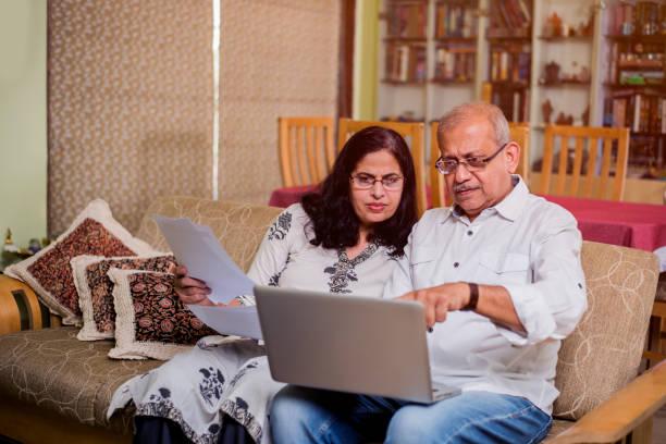 Senior Indian/asian Paar Buchhaltung, die Durchführung von Hausfinanzen und die Überprüfung von Rechnungen mit Laptop, Taschenrechner und Geld, während im heimischen Garten sitzen – Foto