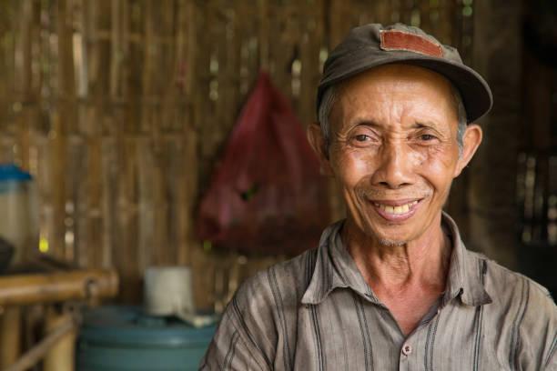 senior indonesian farmer smiling portrait in hut - kultura indonezyjska zdjęcia i obrazy z banku zdjęć