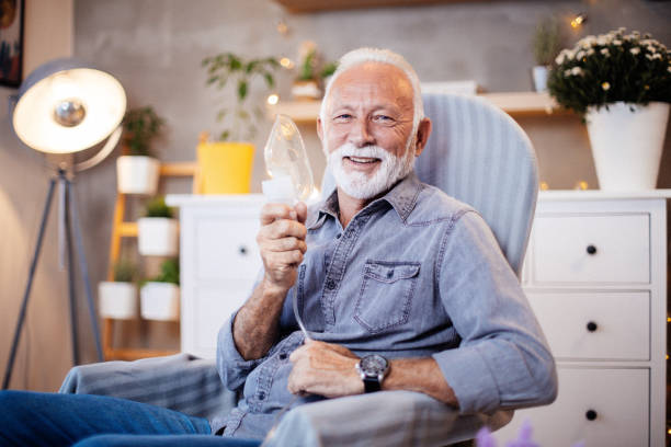 Senior inhalation therapy in progres. Portrait of senior sick man with grey hair at home inhaling. He inhales steam to treat a blocked nose during the day as alternative therapy or traditional cure. Rhinitis treatment at home by inhalation. oxygen stock pictures, royalty-free photos & images
