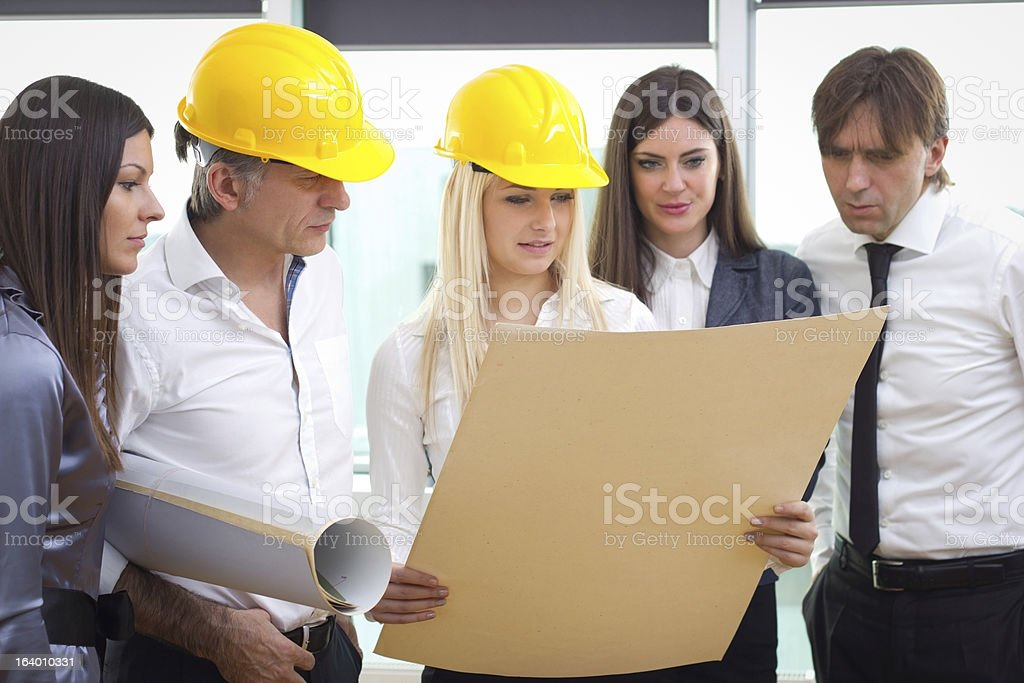Senior investor talking to architect over the blueprints royalty-free stock photo
