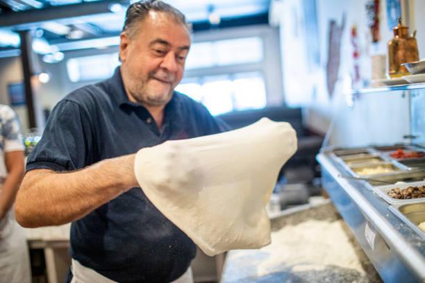 senior italienisch erarbeite pizza teig - italienischer abstammung stock-fotos und bilder