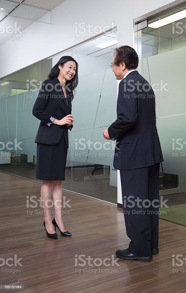 Senior Japanese businessman greats female boss with a gentle bow. stock photo