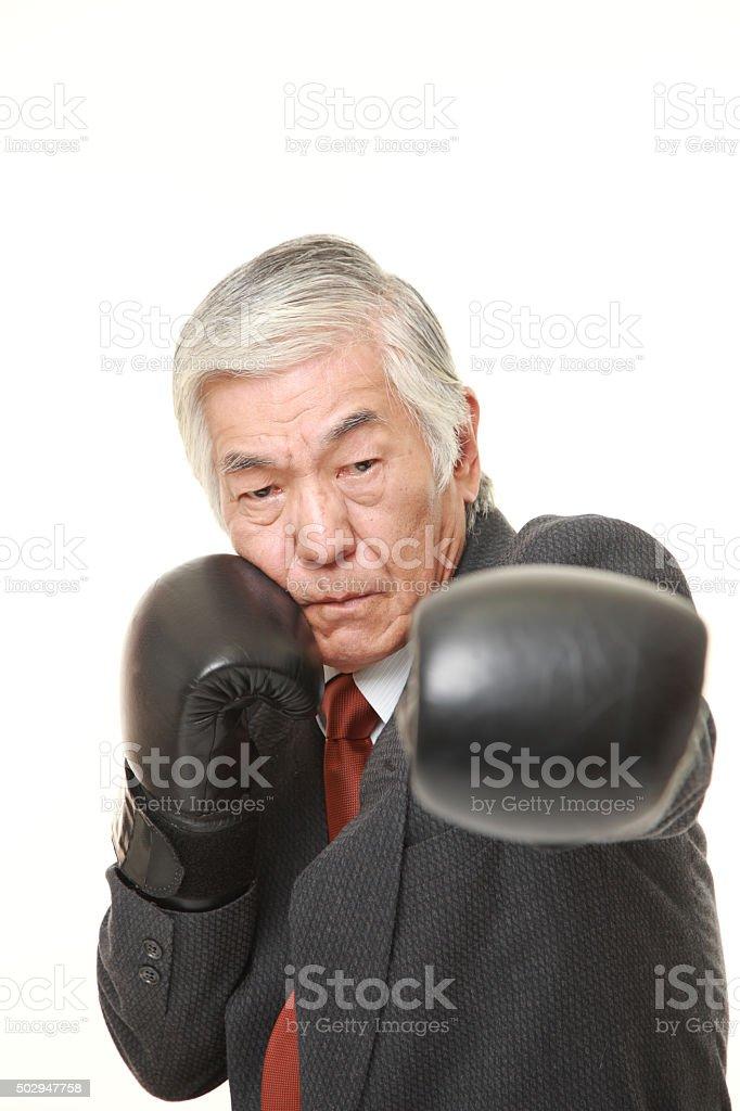 senior Japanese businessman throwing a left jab stock photo