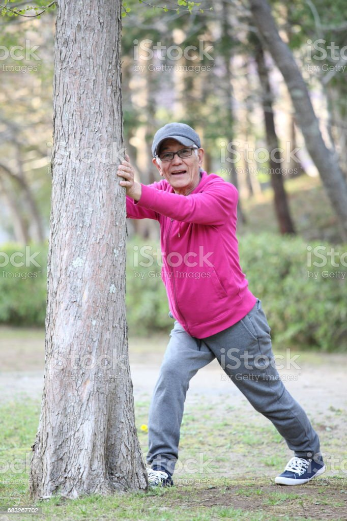 senior Japanese man doing calf stretch by tree stock photo