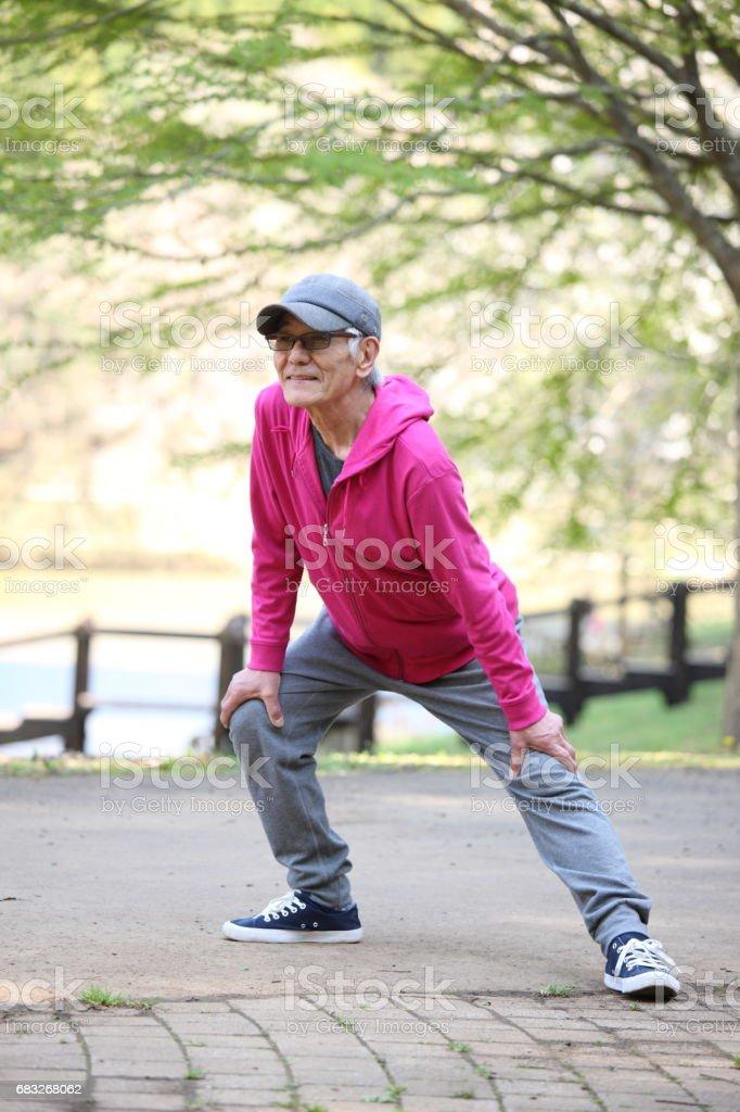 senior Japanese man doing leg stretch outdoor foto de stock royalty-free