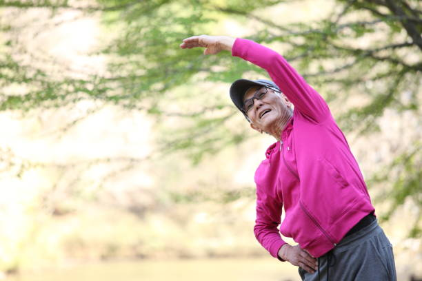 senior Japanese man in pink wear doing standing side bend exercise portrait of senior Japanese man in pink wear doing standing side bend exercise in the park lateral surface stock pictures, royalty-free photos & images