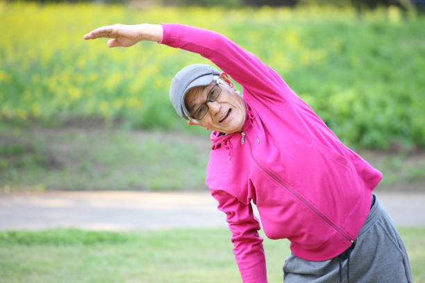 senior Japanese man in pink wear doing standing side bend exercise stock photo