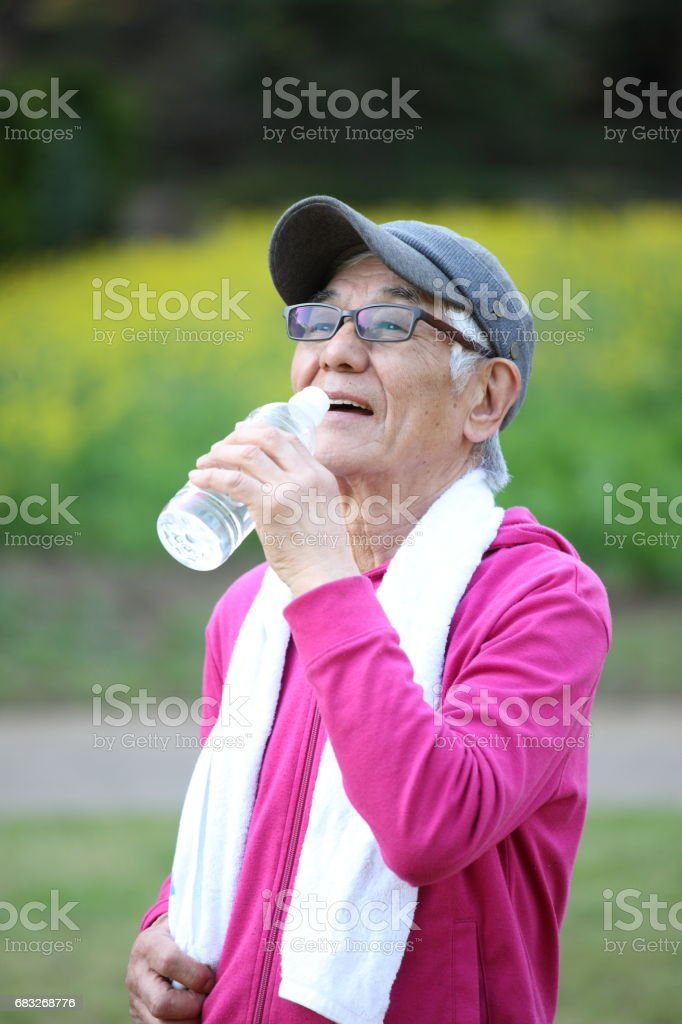 senior Japanese man in pink wear sweaty and thirsty after exercise drinks water outside royalty-free stock photo