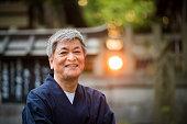 Senior Japanese man wearing a yukata in an outdoor setting
