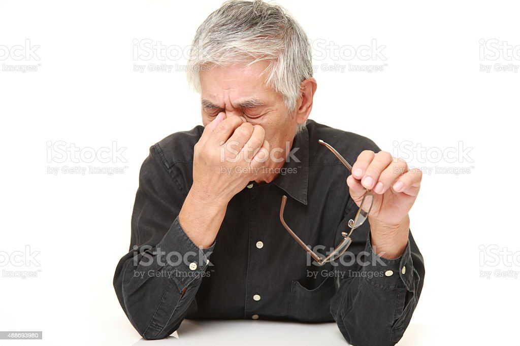 senior Japanese man suffers from Asthenopia stock photo