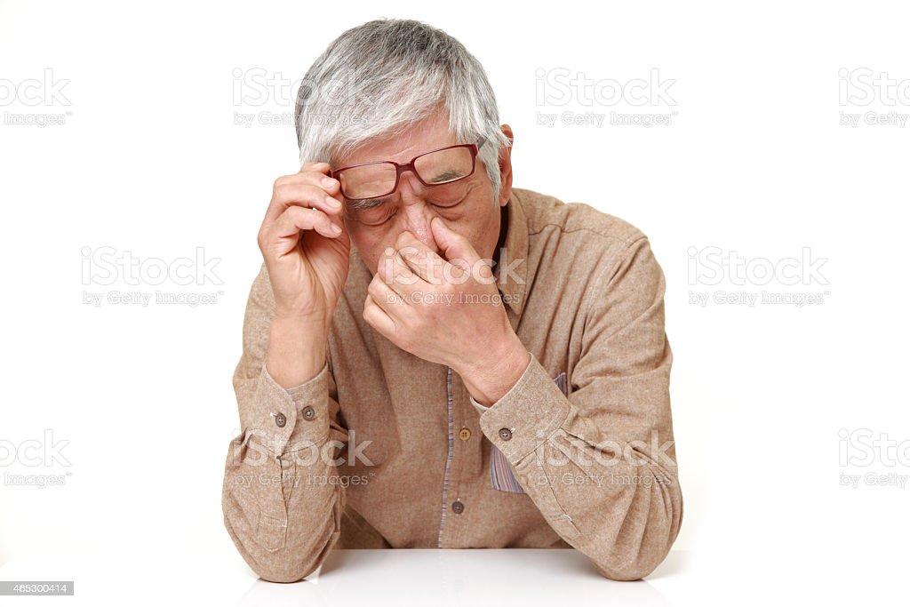 senior Japanese man suffers from headache stock photo