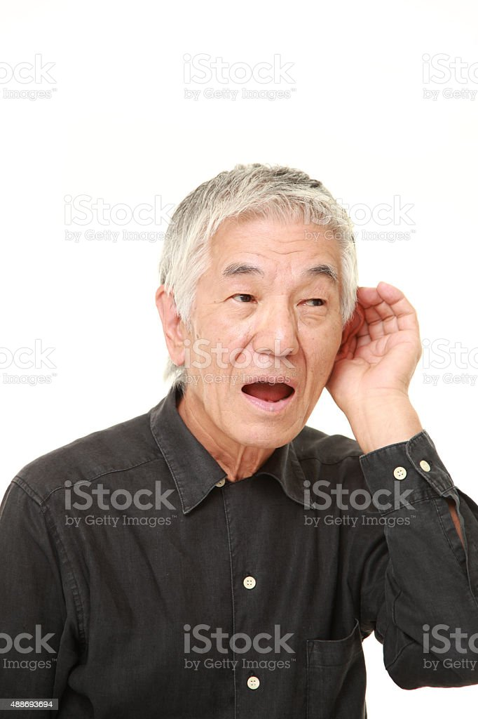 senior Japanese man with hand behind ear listening closely stock photo