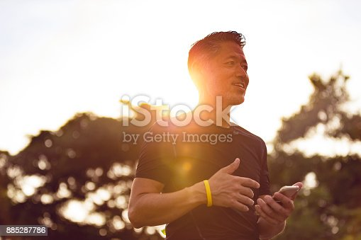 istock Senior Japanese man with his smartphone during sunset 885287786