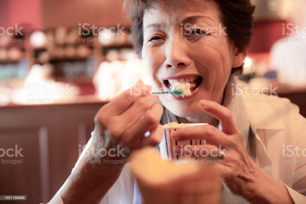 Senior Japanese woman eating icecream stock photo
