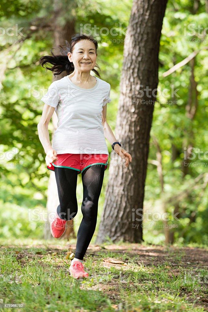 Senior Japanese woman running through woods stock photo