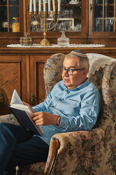 Senior Jew reading book in traditional home