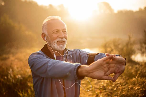Senior Jogger am See in der Morgenzeit strecken Hände – Foto