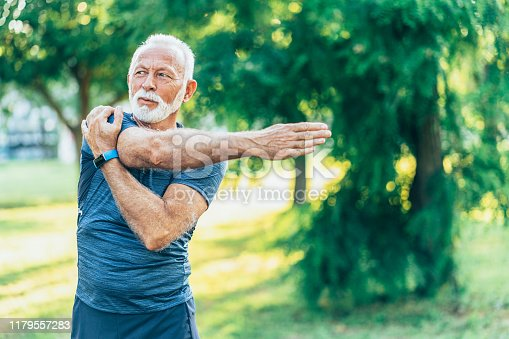 Senior man stretching in the park before jogging