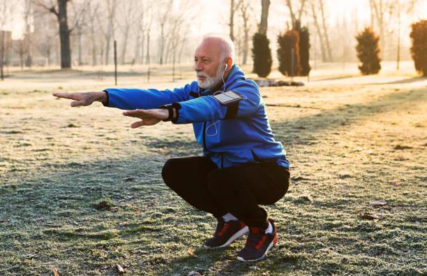 jogger senior haciendo estiramientos - agacharse fotografías e imágenes de stock