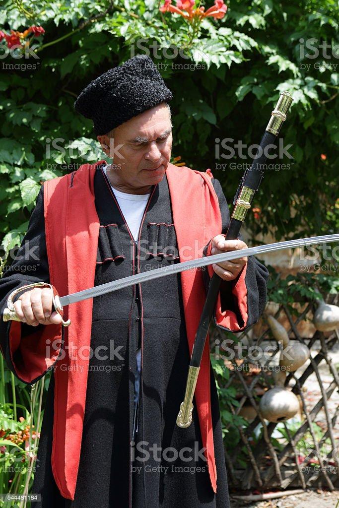 Senior Kuban Cossack checks blade of saber stock photo