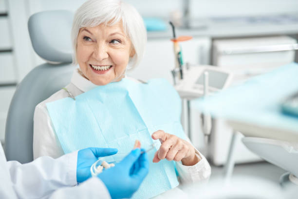 Senior lady asking questions about dental dentures stock photo
