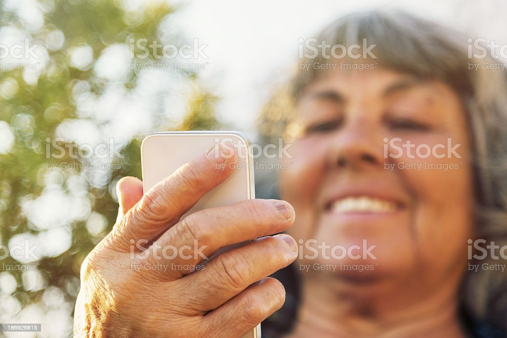 Senior lady checking her mobile phone royalty-free stock photo
