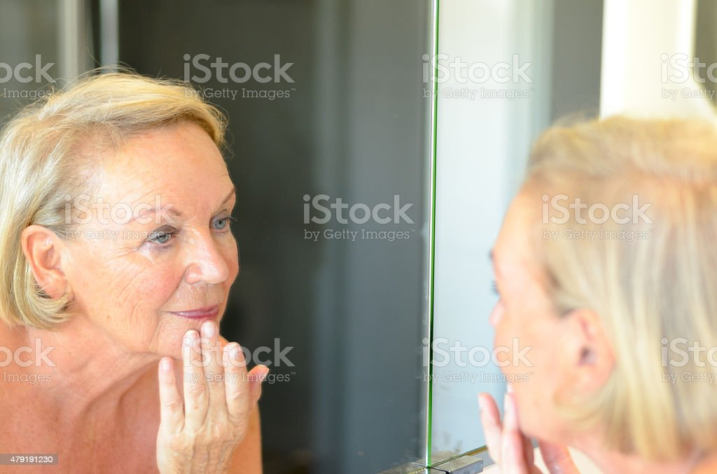 Senior lady checking her skin in the mirror - Royalty-free 2015 Stock Photo
