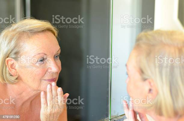 Senior Lady Checking Her Skin In The Mirror Stock Photo - Download Image Now