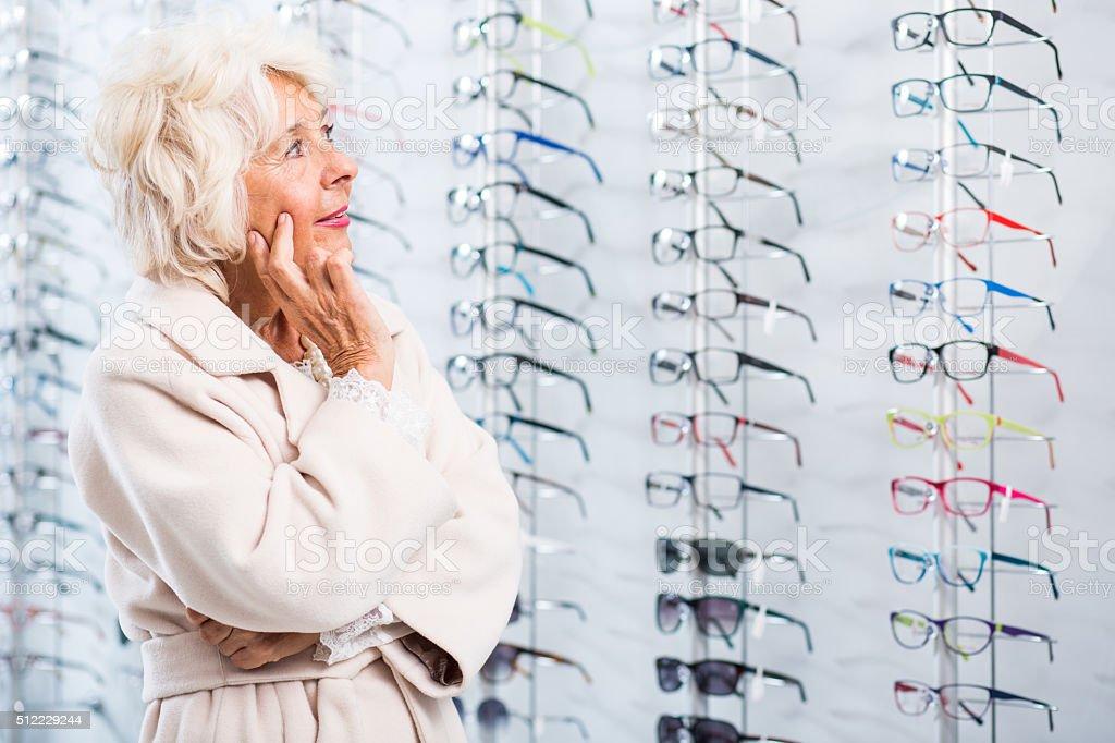 Senior lady chosing eyeglass frames stock photo