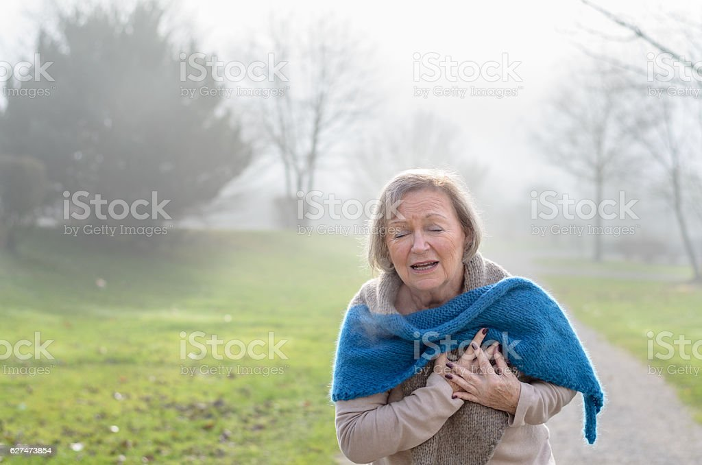 Senior lady clutching her chest in pain - foto de acervo