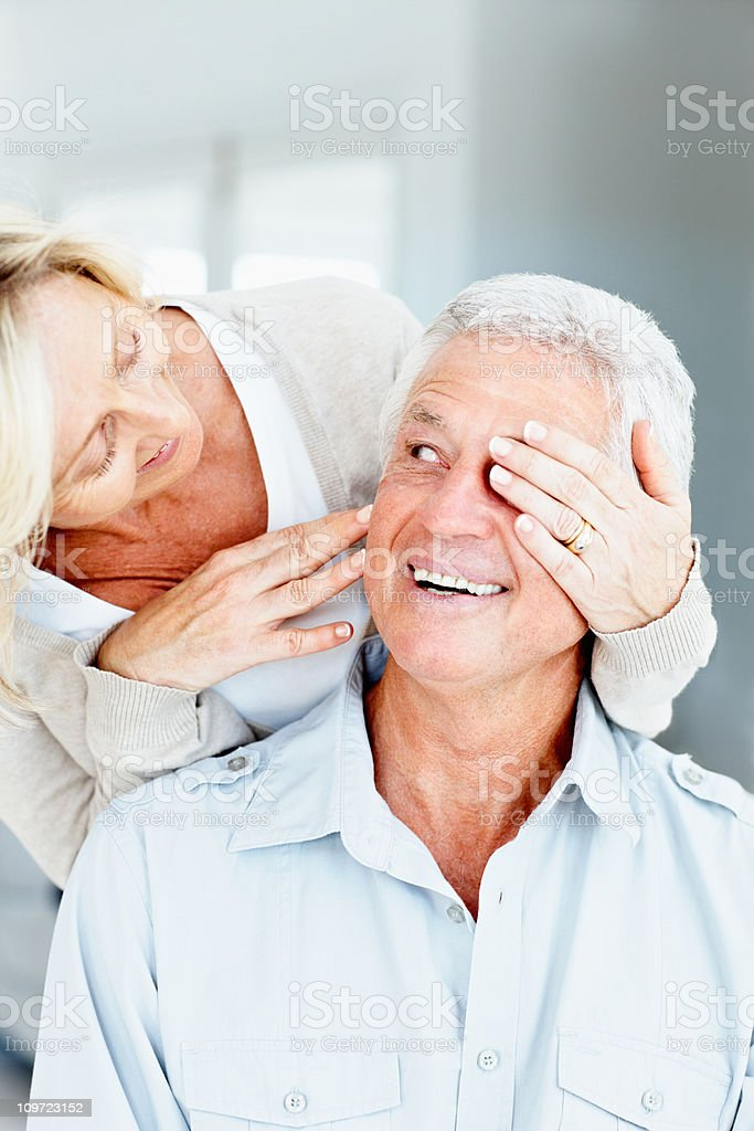 Senior lady covering eyes of her husband stock photo
