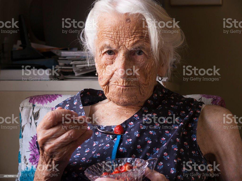 Senior lady eating strawberries stock photo