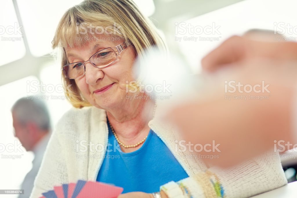 Senior lady enjoying a game of cards royalty-free stock photo