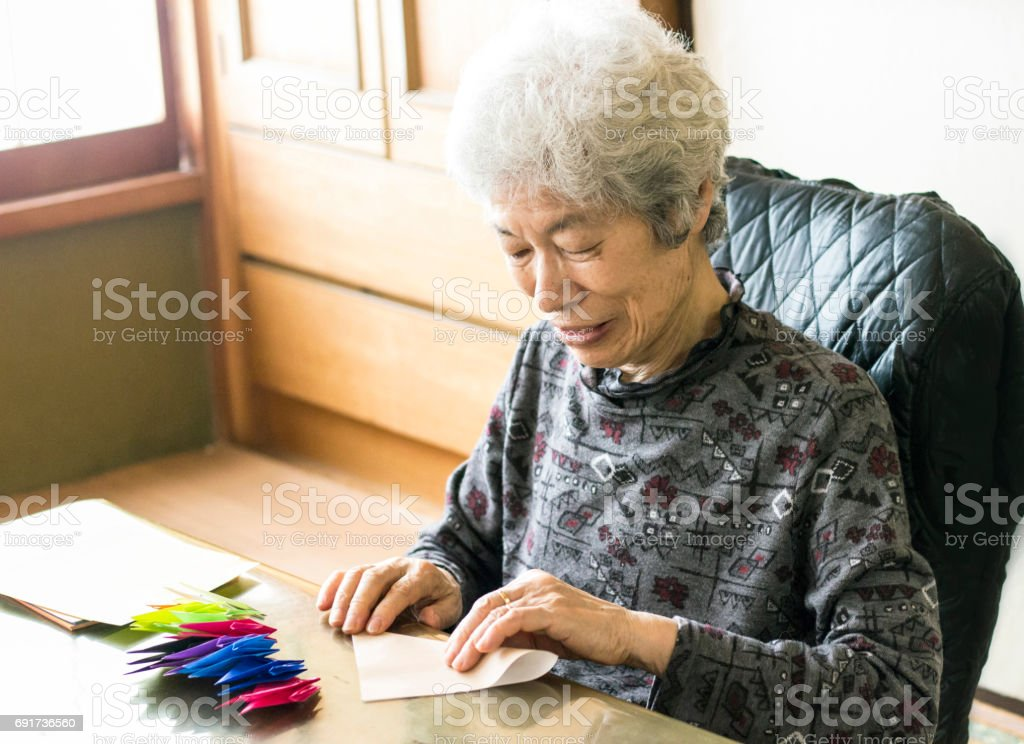 Senior lady folding paper cranes stock photo