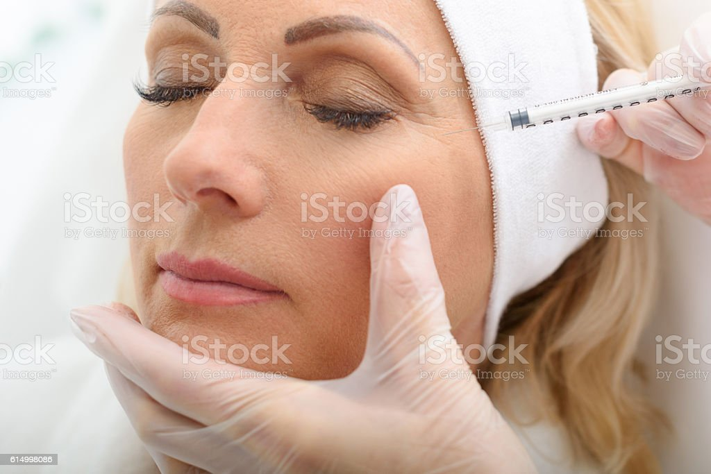 Senior lady having botox injecting procedure stock photo